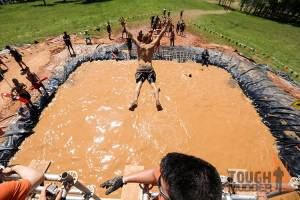 tough-mudder_walk-the-plank_water-jump_swimming-laps_arms-outstretched-overhead
